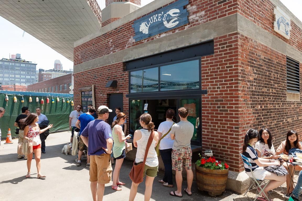 People lined up outside Luke's Lobster on a sunny day.